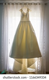 Wedding dress hanging from the curtain of the bride room on her wedding day