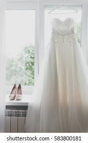 wedding dress hanging near the window