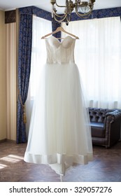 wedding dress hanging on the chandelier in the interior