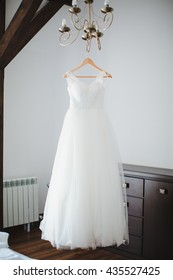 wedding dress hanging on luster at hotel room