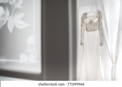 Wedding dress hanging on the wall in the room.