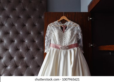Wedding dress hanging on the wardrobe in the bedroom in an expensive hotel. The wedding collection. Classic expensive dress for a wedding or celebration in the room of an expensive hotel. Closeup.