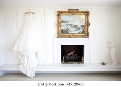 wedding dress hanging on white wall next to fireplace and artwork