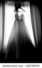 Wedding dress hanging in the window in black and white