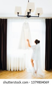wedding dress on the background of the window with tulle and curtains. The bride in robe look at the wedding dress