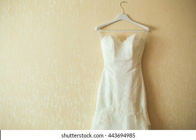 wedding dress on hanger on a wall. Beautiful gown