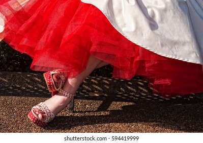 "Wedding Dress and Shoes Beneath her white wedding dress, a bride wears a red net petticoat and red heels in a New Orleans ""destination wedding."""