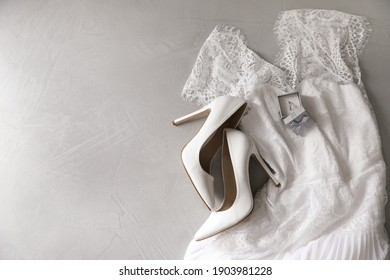 Wedding dress, white high heel shoes and ring on grey background, flat lay. Space for text