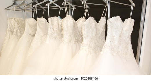 Wedding dresses hanging on a hanger. Fashion look in bridal salon