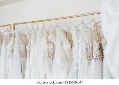 Wedding dresses on hangers in a showroom.