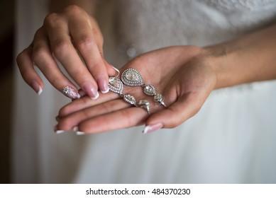 Wedding earrings on a female hand, she takes the earrings, the bride fees morning bride, white dress, wear earrings
