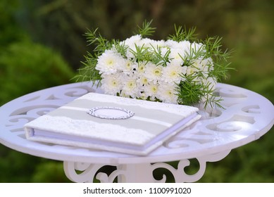 wedding elements, guest book and gift box of flowers on white carved wooden table