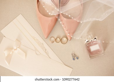 Wedding. Engagement ring and two wedding rings near pink bridal shoes on on high heels, perfume bottle, wedding invitation and earrings for bride. Luxury marriage and wedding concept
