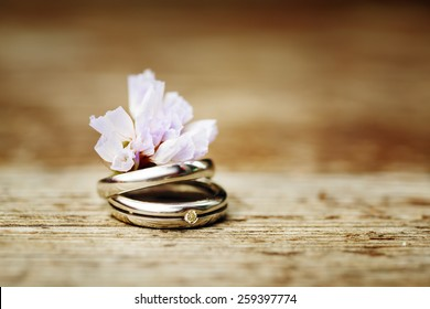 Wedding Engagement Rings Close up with Cute Wild Flower on Wood Background. Rustic Style decoration. Instagram Color Effect.