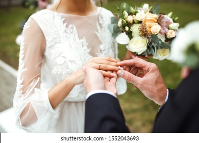 Wedding engagement rings. Married couple exchange wedding rings at a wedding ceremony. Groom put a ring on finger of his lovely wife. Concept wedding details. Happy family. Together.