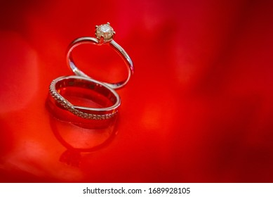 Wedding and engagement rings on red background