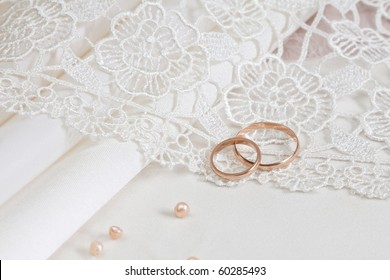 Wedding fabrics and lace and two gold rings.