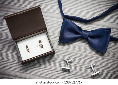 Wedding fashion accessories. Grooms bowtie, golden rings and cufflinks.