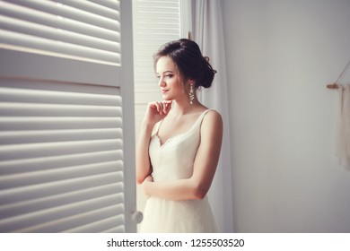 Wedding fashion bride in dress posing near window