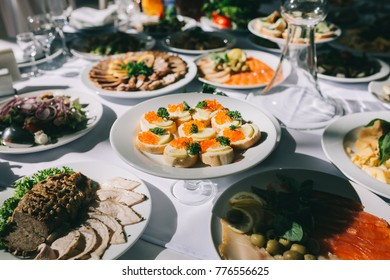 Wedding feast table with different dishes and bread with red caviar.