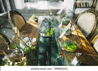 Wedding , festive decor with flower compositions and succulents in florariums. Table layout. Table of newly married. Restaurant interior.