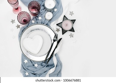 Wedding or festive table setting. Plates, wine glasses, candles and cutlery with gray decorative textile on white background. Beautiful arrangement.