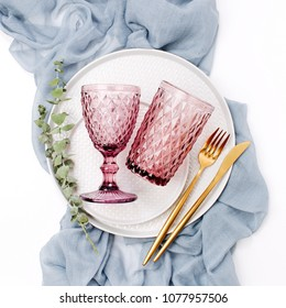 Wedding or festive table setting. Plates, wine glasses and cutlery with gray decorative textile on white background. Beautiful arrangement.