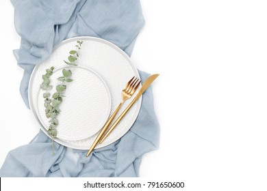 Wedding or festive table setting. Plates and cutlery with gray decorative textile on white background. Beautiful arrangement.