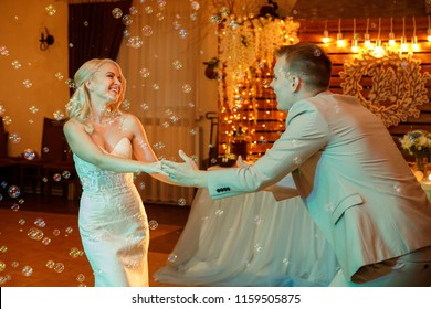 Wedding. First wedding dance of stunning bride and attractive groom, cheerfully smiling, bubbles. Love. Marriage. Indoors.