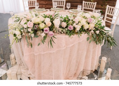 Wedding floral table decoration with candles in transparent vases