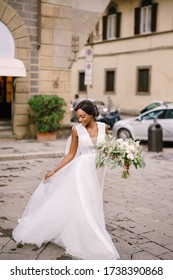 Wedding in Florence, Italy. African-American bride in a white dress with a long veil and a bouquet in her hands.