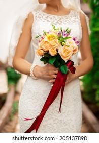 Wedding flowers bouquet. bride holding beautiful orange roses.