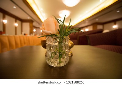 Wedding flowers displayed on a wooden log in the centre of a table at a wedding reception