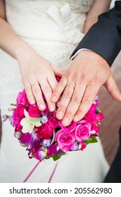 Wedding flowers and hands of a newly-married couple with wedding rings