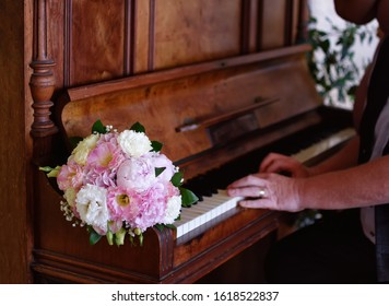 Wedding flowers lie on the keys of the piano. Hands of man playing an old piano.