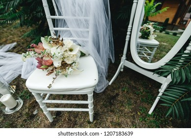 wedding flowers on a white chair with decor