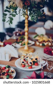 Wedding food on the background of decor in a burgundy color in the restaurant with flowers