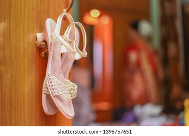 Wedding footwear sandals hanging on the the door as the Indian bride gets ready for the ceremony in the background looking at a mirror. Hindu weddings in India are a very lavish celebration