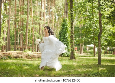 Wedding in the forest. Wedding in the summer in the park. Bride in a very beautiful wedding dress is walking around the garden on her wedding day. The bride is running