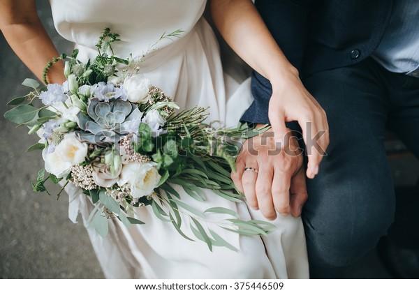 Mariage. La fille en robe blanche et un gars en costume assis sur une chaise en bois tiennent un joli bouquet de fleurs blanches, bleues, roses et vertes, décorées de ruban de soie