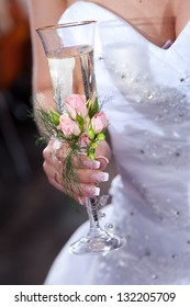wedding glass decorated by flowers in hands of bride