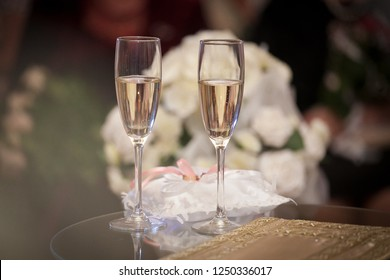 wedding glasses with a wedding bouquet in the background, pillow with wedding rings, wedding accessories