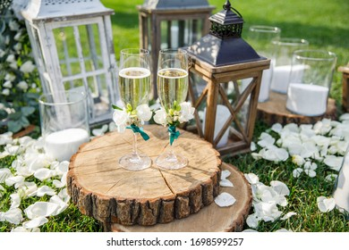 wedding glasses with champagne stand on a wooden tray near the candles and the place of the wedding ceremony