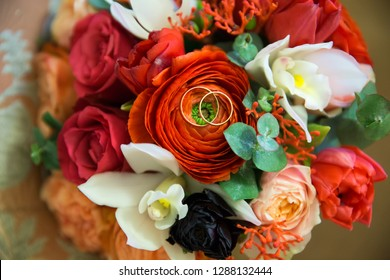 Wedding gold rings on a bouquet of flowers
