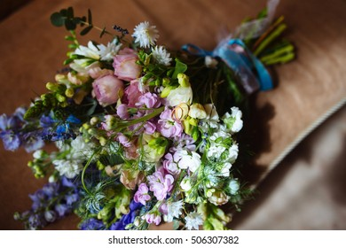 Wedding gold rings on a bouquet of wildflowers