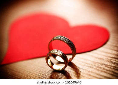 Wedding golden rings and a big red heart on wooden table in a soft gold vintage light.