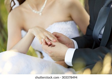 At the wedding, the groom puts the ring on the bride's finger. Hand  with  rings  . Outdoors