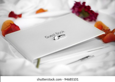 Wedding guest book laid on white silk and surrounded by flower petals