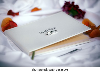 Wedding guest book on a white silk tablecloth