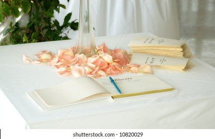 Wedding guest book and order of service sheets on table with rose petals